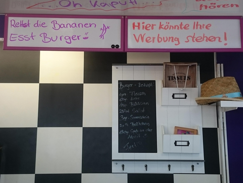 Der Burgerstand auf dem Campinggelände ist bunt bemalt mit humoristischen Werbesprüchen...