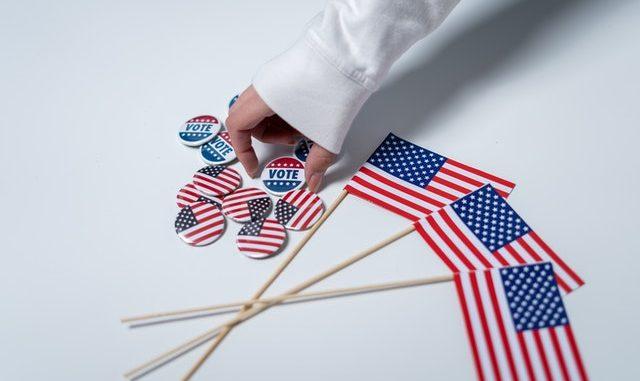 """""""Vote""""-Buttons und US-Flaggen liegen auf einem Tisch"""